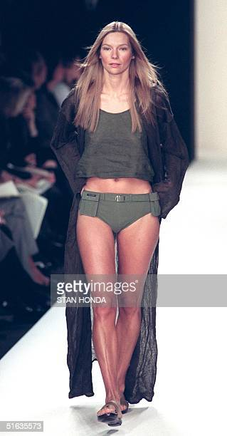 A model wears a brown floor length linen coat over a fatigue tank top and belted bikini during the Ralph Lauren fashion show 04 November in New York...