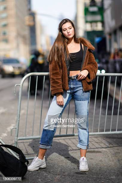 A model wears a brown fluffy coat a black cropped tank top blue patchwork denim jeans white Fila sneakers during New York Fashion Week Fall Winter...