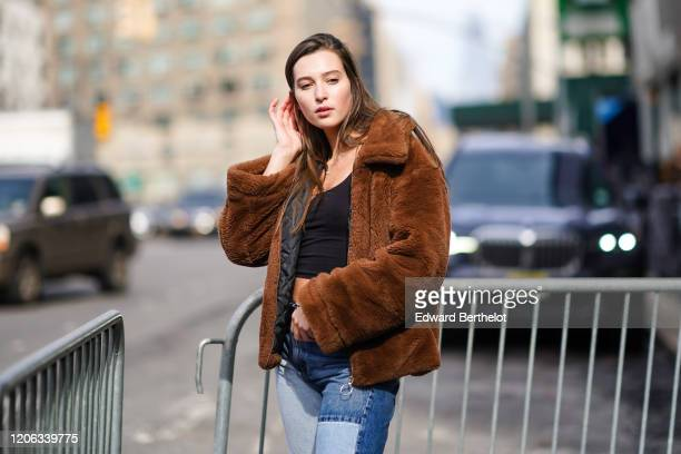 A model wears a brown fluffy coat a black cropped tank top blue patchwork denim jeans during New York Fashion Week Fall Winter 2020 on February 12...