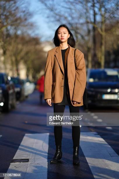 Model wears a brown oversized blazer jacket, leggings, black leather boots, outside Rokh, during Paris Fashion Week - Womenswear Fall/Winter...