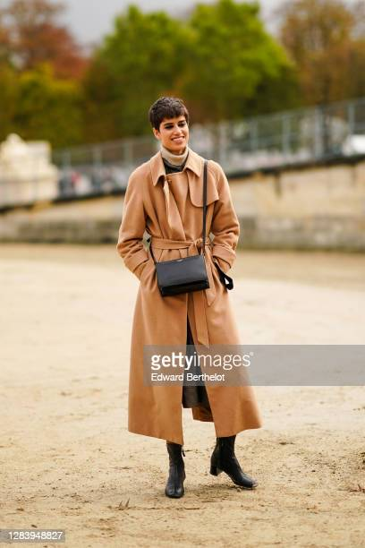 Model wears a brown trench coat, a wool turtleneck pullover, a black leather bag, black leather boots, outside Dior, during Paris Fashion Week -...