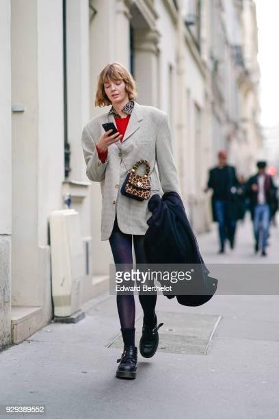 A model wears a checked blazer jacket a leopard print bag outside APC during Paris Fashion Week Womenswear Fall/Winter 2018/2019 on March 5 2018 in...
