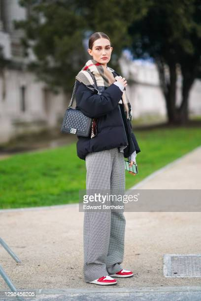 Model wears a checked plaid wool scarf, a black winter puffer jacket, a black leather quilted Chanel bag, gray flared pants, red and white sneakers...
