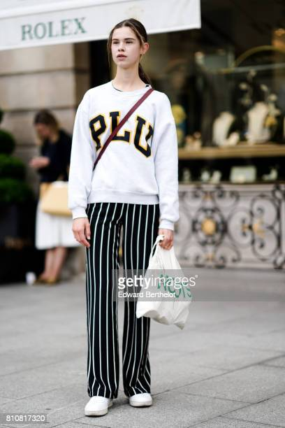 A model wears a chite pull over striped pants white sneakers outside the Schiaparelli show during Paris Fashion Week Haute Couture Fall/Winter...