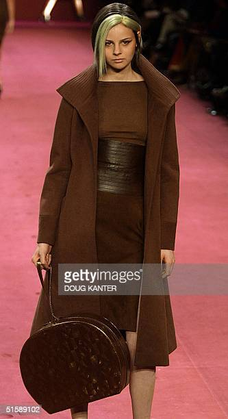 A model wears a cocoa cotton moleskin funnel coat cocoa cashmere boatneck sweater cocoa suede skirt and chocolate leather belt at the BCBG Max Azria...