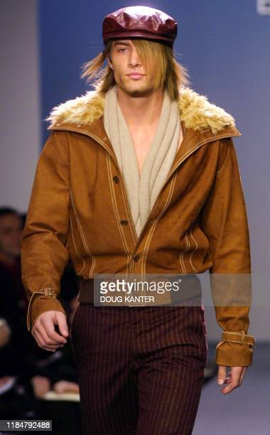 A model wears a cognac nappa bomber jacket with faux fur trim cranberry wool pinstripe trousers and a cranberry leather bugatti at the BCBG Max Azria...