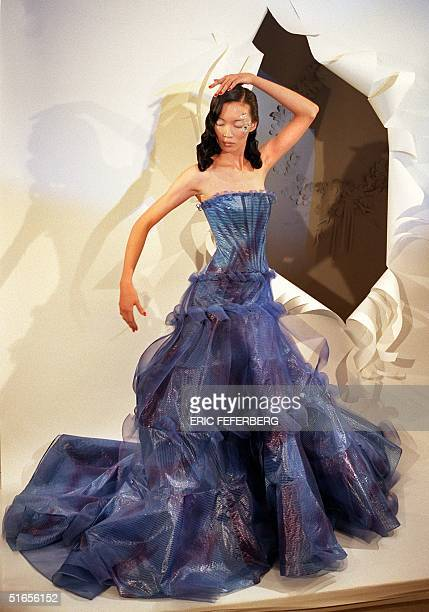 A model wears a corolla gitane blue cellophane bustier dress worked in graduated bands of serpentined bold blue horsehair designed by John Galliano...
