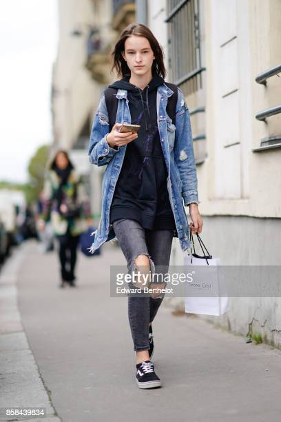 A model wears a denim jacket and ripped jeans outside Giambattista Valli during Paris Fashion Week Womenswear Spring/Summer 2018 on October 2 2017 in...
