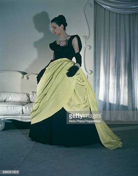 A model wears a formal evening gown by Balenciaga in black slipper stain with yellow faille draped overskirt from the Spring collection in Paris...