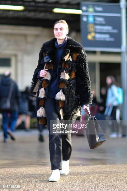 A model wears a fur coat outside the Olivier Theyskens show during Paris Fashion Week Womenswear Fall/Winter 2017/2018 on February 28 2017 in Paris...