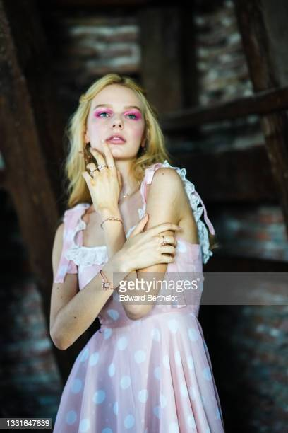 Model wears a gold pink large earring, a pale pink and white polka dots tank-top / square neck short dress with white ruffled lace on the borders and...