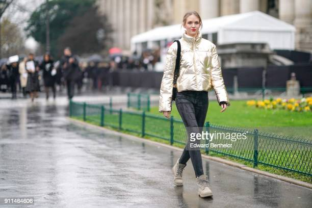 A model wears a gold shiny glitter puffer coat black denim jeans gray shoes outside Chanel during Paris Fashion Week Haute Couture Spring/Summer 2018...