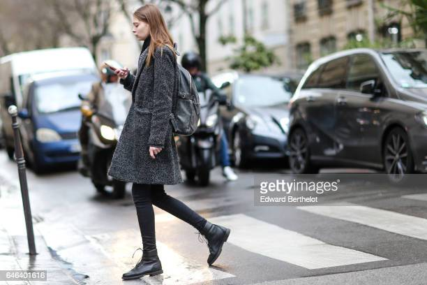 A model wears a gray coat black pants and black shoes outside the JOUR/NE show during Paris Fashion Week Womenswear Fall/Winter 2017/2018 on February...