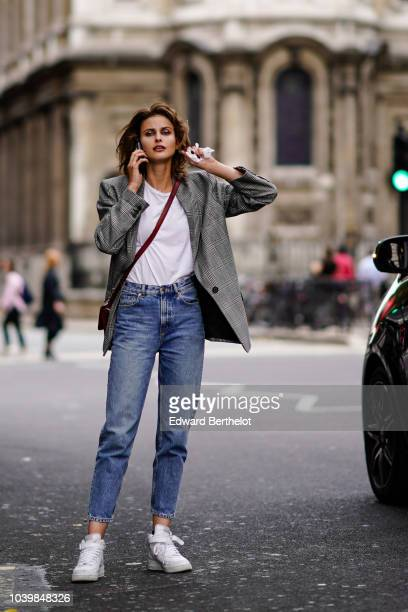 A model wears a gray jacket a white top blue jeans white sneakers shoes during London Fashion Week September 2018 on September 18 2018 in London...