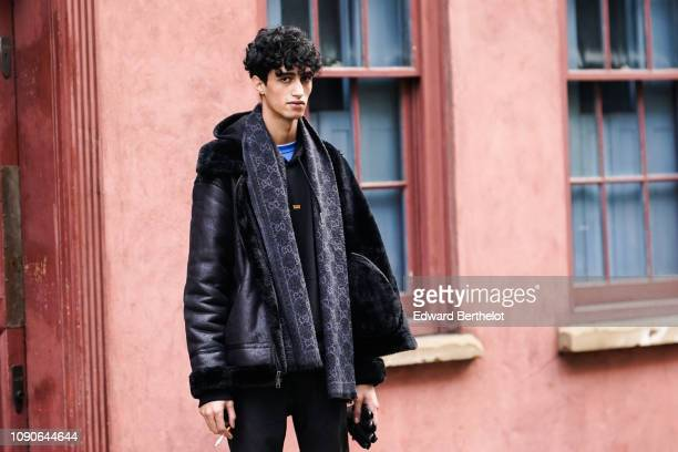 A model wears a gray scarf a black aviator jacket black pants black sneakers during London Fashion Week Men's January 2019 on January 05 2019 in...