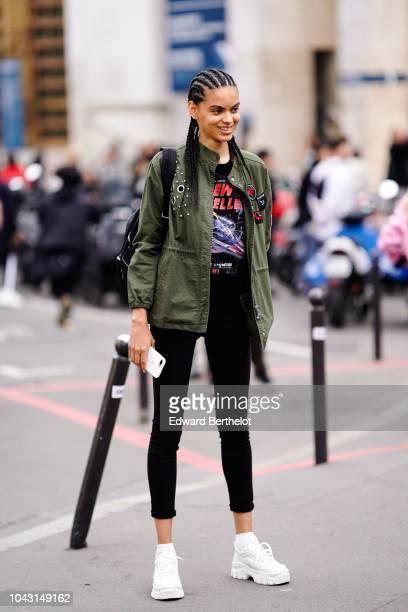 A model wears a green khaki jacket black leggings white sneakers outside Issey Miyake during Paris Fashion Week Womenswear Spring/Summer 2019 on...