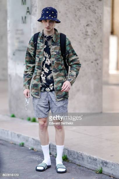 A model wears a hat a military camouflage print jacket a flower print top gray shorts white socks sandals outside the 22/4 Hommes show during Paris...