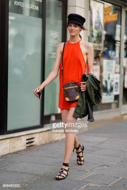A model wears a hat an orange dress a Vuitton bag outside the Valentino show during Paris Fashion Week Haute Couture Fall/Winter 20172018 on July 5...