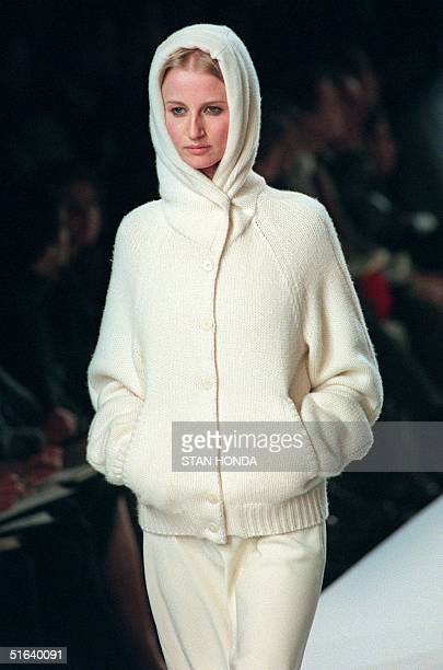 A model wears a hooded beige sweater over beige trousers during the Ralph Lauren FallWinter fashion show 01 April in New York The collection is part...