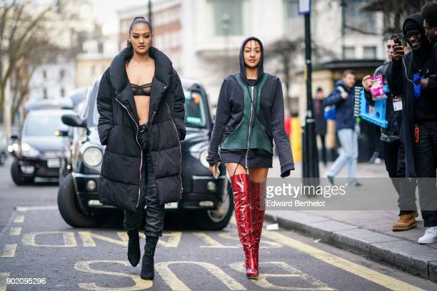 A model wears a hoodie a short red snake print thigh high leather boots during London Fashion Week Men's January 2018 at on January 6 2018 in London...