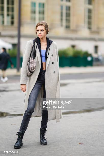 Model wears a hoodie sweater, a gray wool long coat, a pale blue bras, black jeans, a bag, black leather boots, outside Chanel, during Paris Fashion...
