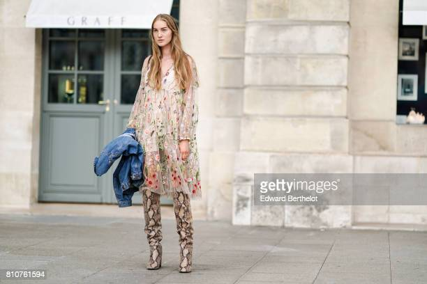 A model wears a lace mesh dress with embroidered flowers and snake print boots outside the Schiaparelli show during Paris Fashion Week Haute Couture...