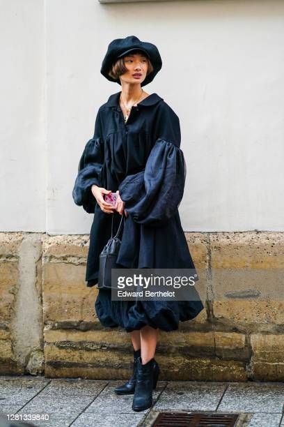 A model wears a large beret hat a black shirt / ruffled dress with puff sleeves a black leather cubeshaped bag black leather pointy shoes outside...