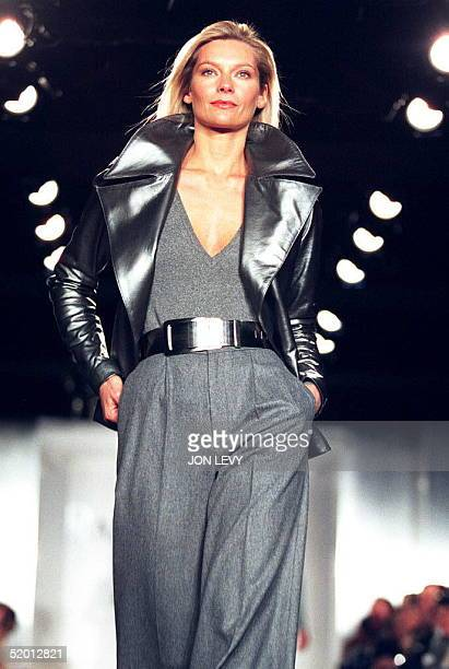 A model wears a metallic leather collar coat over a grey vneck top with matching suit pants in the Ralph Lauren Fall 1997 collection 09 April in New...