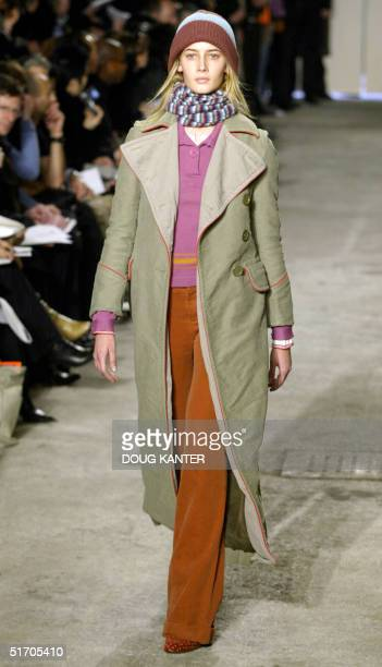 A model wears a moleskin army coat mustard stripe polo sweater long sleeve sweater with red band cuff cavalry cuffed pants wool hat and blurred...
