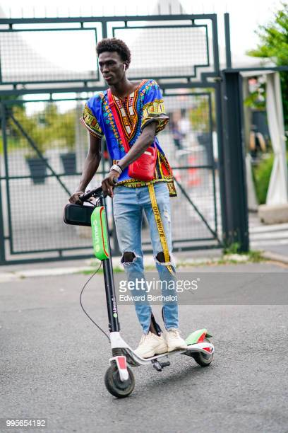 A model wears a multicolor printed top a yellow offwhite belt blue ripped jeans white sneakers shoes a red leather shoulder strap bag and rides an...