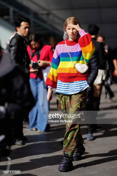 Model wears a multicolor striped rainbow wool pullover, a heart shaped bag, a blue and white striped t-shirt, green and brown military camouflage...