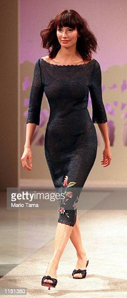 A model wears a navy raffia crocheted dress adorned with a floral hemline designed by Stella McCartney during a show presenting her spring fashion...