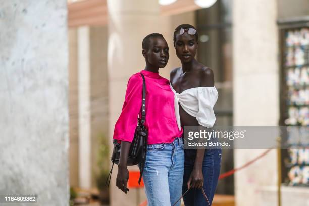 A model wears a neonpink top a black bag jeans A model wears sunglasses a white offshoulder crop top jeans during Paris Fashion Week Haute Couture...