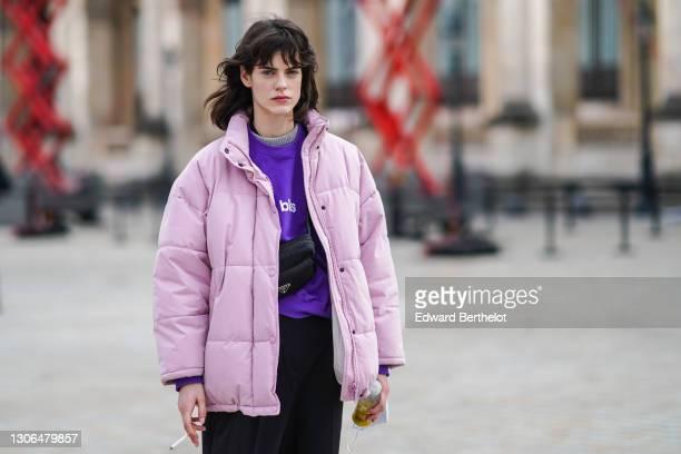 Model wears a pale pink oversize long puffer winter coat, a purple pullover, a black Prada fanny pack bag, black sportswear jogger pants, on March...