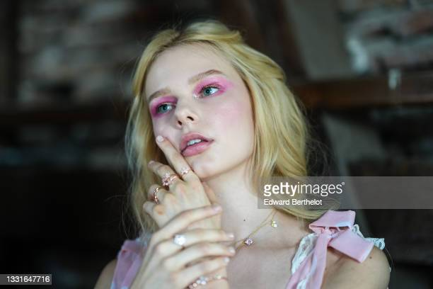 Model wears a pale pink shoulder knotted tank-top / square neck short dress with white ruffled lace on the borders, gold pink and diamond rings,...