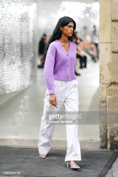Model wears a pale purple wool cardigan with buttons, white pants, pointy shoes, outside Paco Rabanne, during Paris Fashion Week - Womenswear Spring...