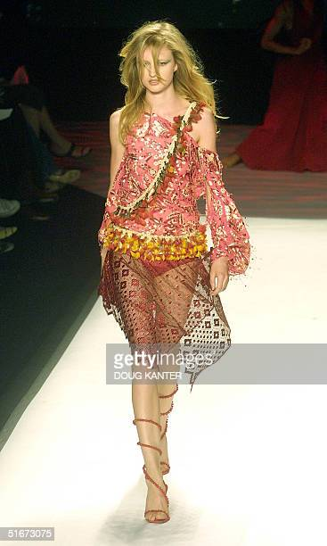 A model wears a pink abstract print silk chiffon top with sequin applique and red guipure lace skirt with irregular hem at the Carlos Miele Spring...