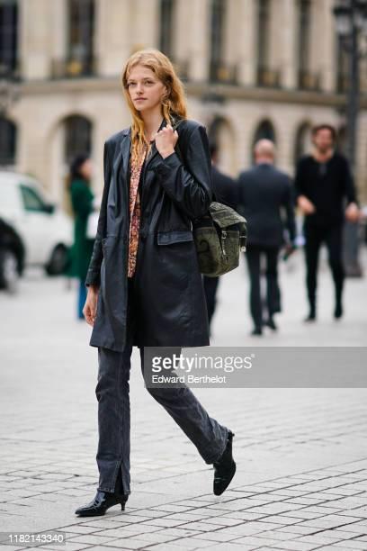 Model wears a pink and orange floral print top, a black leather coat, a Dior khaki messenger bag, black denim ripped hem pants, shiny patent leather...
