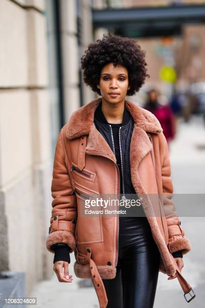 A model wears a pink aviator jacket with wool inner lining shiny leggings a black jacket during New York Fashion Week Fall Winter 2020 on February 12...
