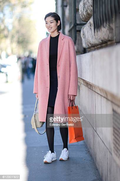 A model wears a pink jacket a black top black pants and white shoes outside of the Hermes show during Paris Fashion Week Spring Summer 2017 on...