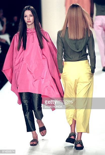 A model wears a pink poncho over black trousers as she passes a second model wearing a gray hooded knit top over yellow trousers during the Ralph...