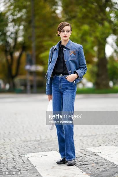 Model wears a Prada blue denim jacket, a black shirt, blue jeans, black leather shoes, outside Chanel , during Paris Fashion Week - Womenswear Spring...