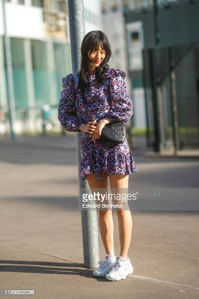 A model wears a purple floral print frilly mini dress a black heartshaped bag white Acne Studios sneakers outside Acne during Paris Fashion Week...