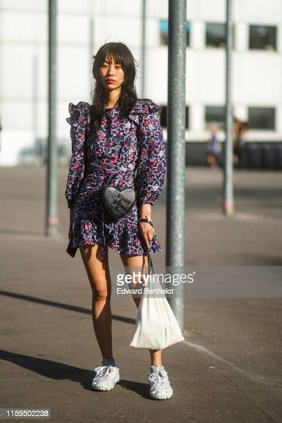 Model wears a purple floral print frilly mini dress, a black heart-shaped bag, white Acne Studios sneakers, outside Acne, during Paris Fashion Week -...