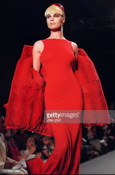 Model wears a red cashmere maillot dress with a matching satin nylon sheared mink polar puffer jacket in the showing of the Halston Fall 1997 fashion...