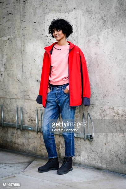 A model wears a red coat and a pink top blue jeans outside the Lemaire show during Paris Fashion Week Womenswear Spring/Summer 2018 on September 27...