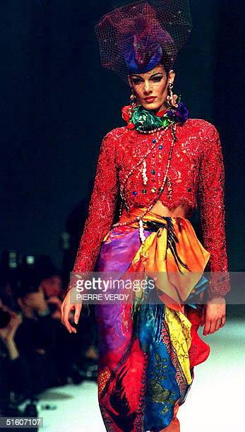 Model wears a red embroided jacket with a hand-painted muslin skirt worn on top of orange muslin pants strikes during the presentation of the 1994...