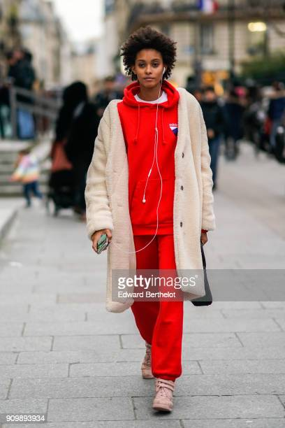 A model wears a red hoodie sweater a beige wool coat outside Viktor Rolf during Paris Fashion Week Haute Couture Spring/Summer 2018 on January 24...