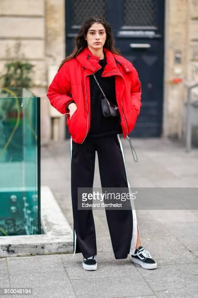 A model wears a red puffer coat a black bag black flare striped sportswear pants sneakers shoes outside Viktor Rolf during Paris Fashion Week Haute...