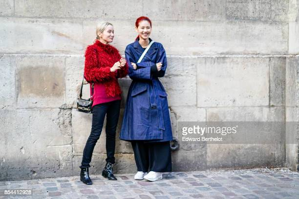 A model wears a red pull over a model wears a blue rain coat outside Koche during Paris Fashion Week Womenswear Spring/Summer 2018 on September 26...